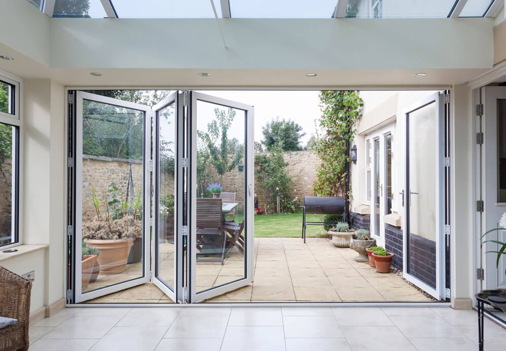 White aluminium bifold partially open leading out onto garden