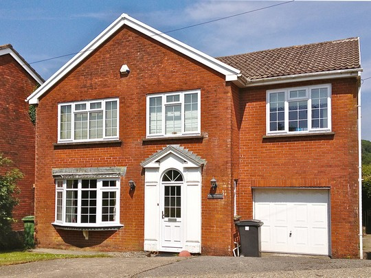 detached red brick house with white upvc windows
