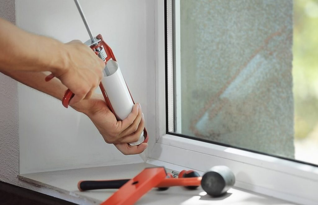 A window repair man with a sealant gun