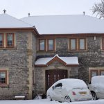 snow covered house with golden oak effect double glazed windows